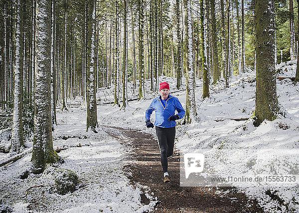 Senior man jogging in snowy woods