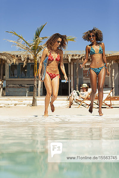 Happy young women in bikinis on sunny beach
