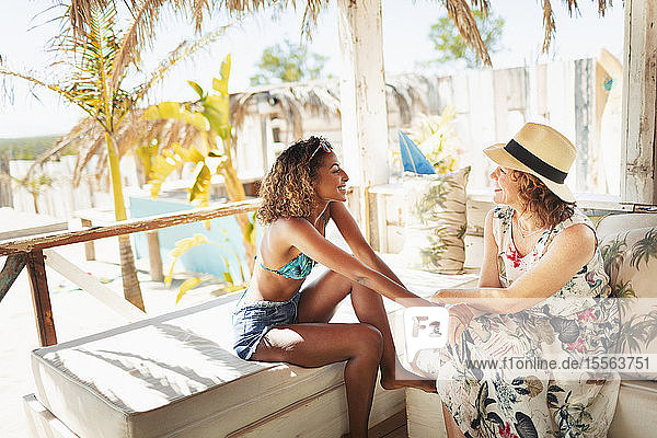 Mother and adult daughter relaxing  talking on beach hut patio