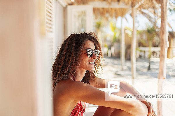 Happy  carefree young woman relaxing on sunny beach hut patio