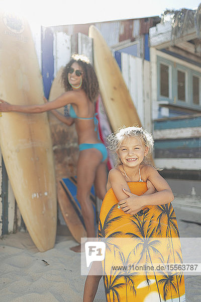 Portrait happy mother and daughter with surfboard and boogie board on sunny beach