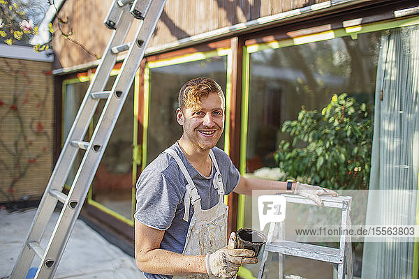 Portrait confident male painter with ladder painting home exterior