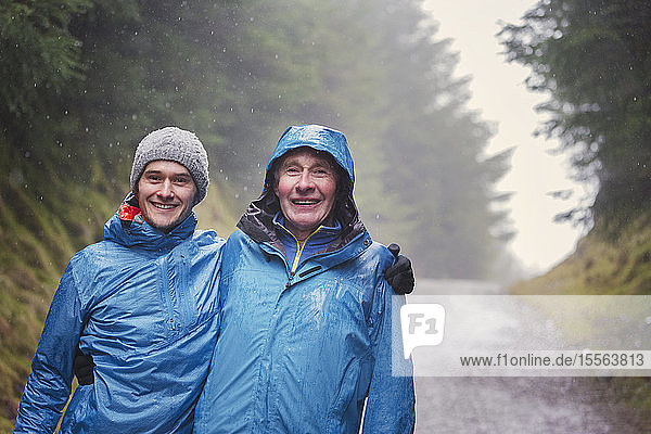 Portrait father and son hiking in rain