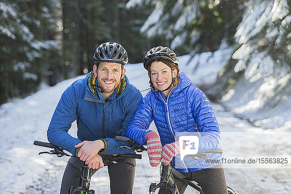 Happy couple mountain biking in snow