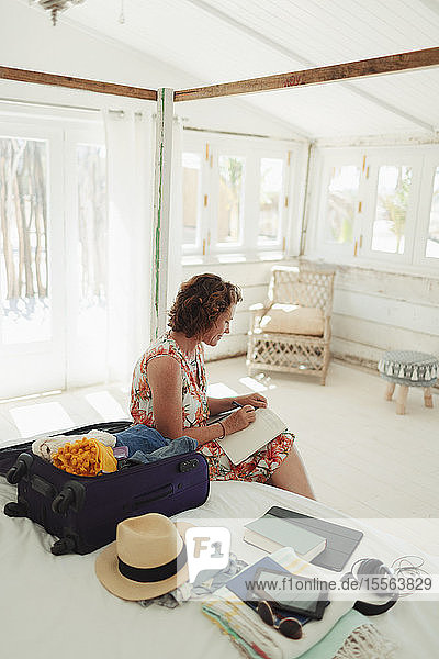 Woman writing in journal next to suitcase in beach hut bedroom