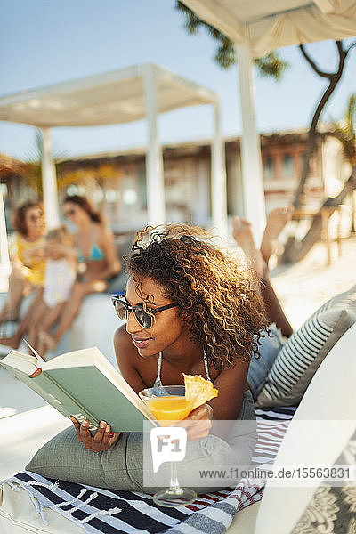 Carefree woman relaxing  reading book and drinking cocktail on beach patio