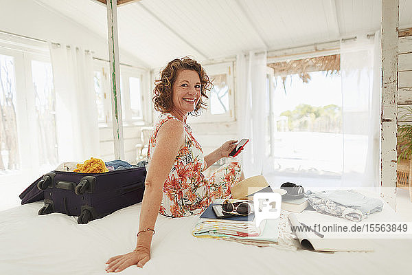 Portrait happy woman unpacking suitcase on beach house bed