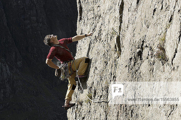 Male rock climber scaling rock face  looking up