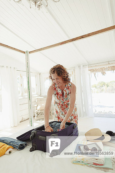 Woman unpacking suitcase in beach hut bedroom