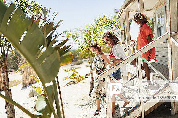 Women friends on sunny beach hut steps