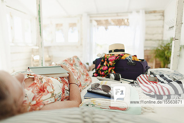 Woman with book relaxing on bed next to suitcase in sunny beach hut bedroom