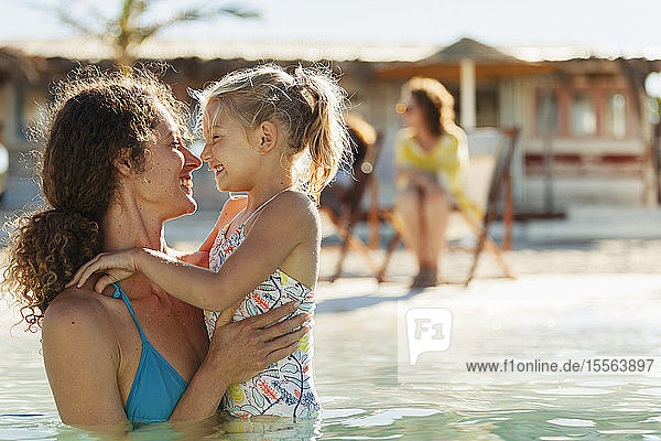 Happy  affectionate mother and daughter swimming in sunny ocean