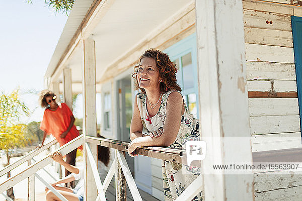 Happy woman relaxing on sunny beach hut patio