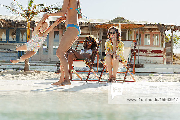 Women relaxing and playing with girl on sunny beach