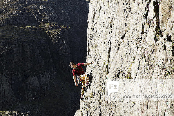 Male rock climber scaling large rock face  looking down over shoulder