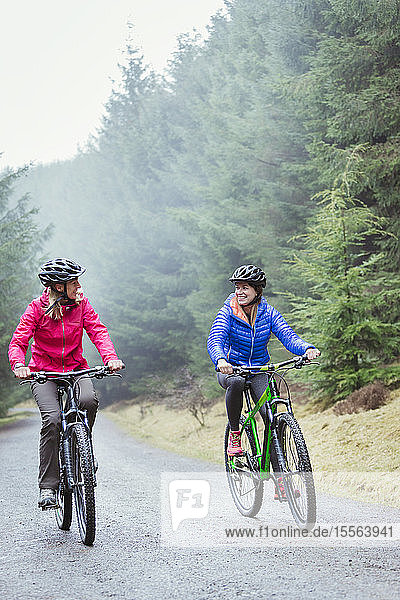 Women mountain biking in woods