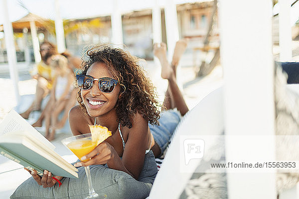 Portrait happy  carefree young woman reading book and drinking cocktail on beach