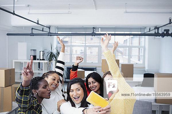 Happy businesswomen celebrating new office  taking selfie