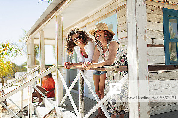 Mother and adult daughter relaxing on sunny beach hut patio
