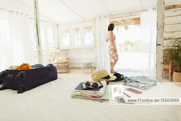 Woman standing in beach hut doorway beyond suitcase and belongings on bed