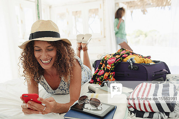 Happy young woman using smart phone  unpacking suitcase on beach hut bed