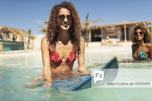 Portrait smiling young woman on surfboard in sunny ocean