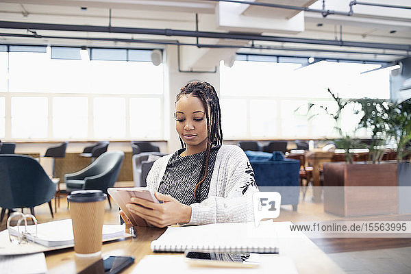 Businesswoman using digital tablet in open plan office