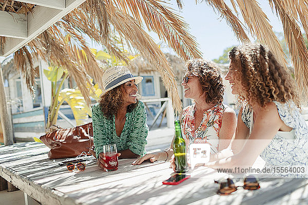 Women friends drinking cocktail and beer and sunny beach bar