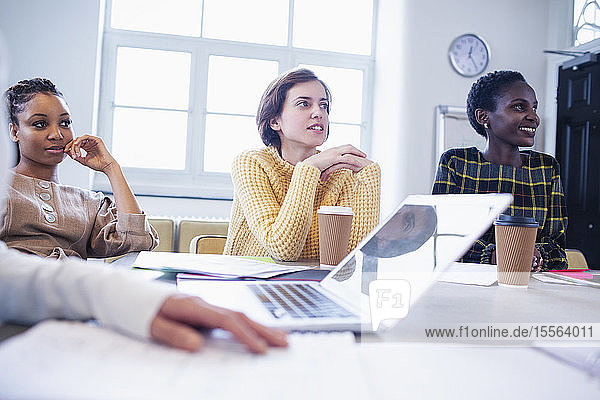 Businesswomen listening in conference room meeting