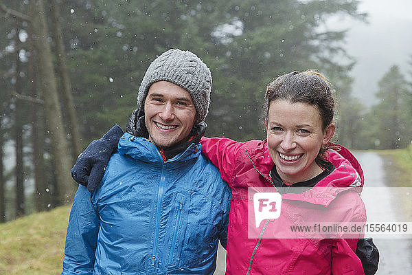 Happy couple hiking in rain
