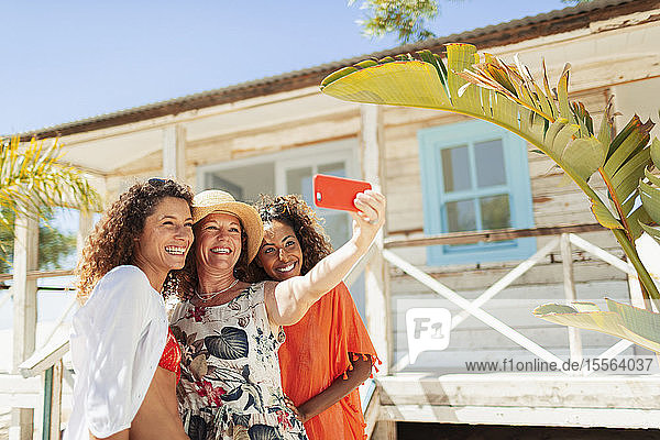 Happy mother and adult daughters taking selfie outside sunny beach hut