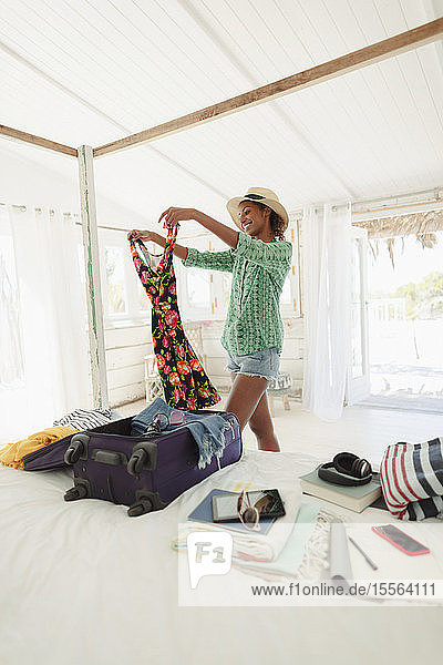 Happy woman unpacking suitcase in beach house bedroom