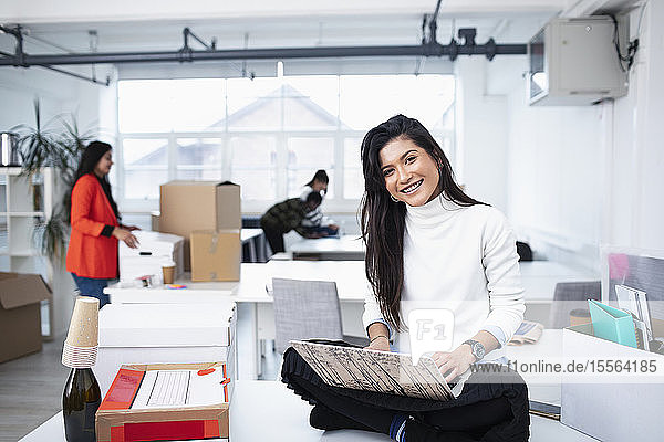 Portrait smiling  confident businesswoman using laptop in new office