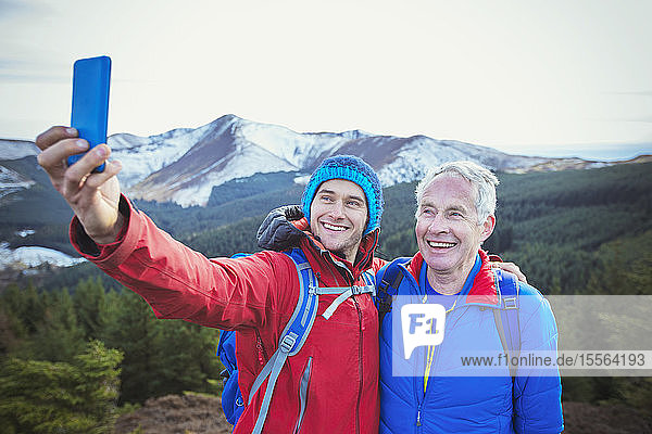 Father and son taking selfie with mountains in background