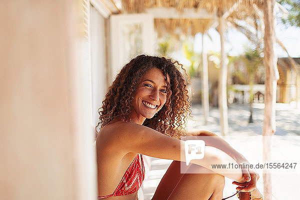 Portrait happy young woman in bikini relaxing on sunny beach hut patio