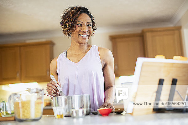 Portrait smiling  confident woman cooking in kitchen