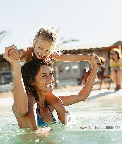 Happy mother and daughter playing in sunny ocean