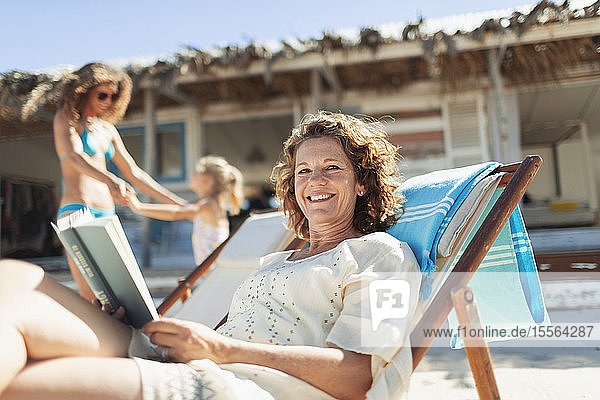 Portrait happy woman reading book  relaxing on sunny beach