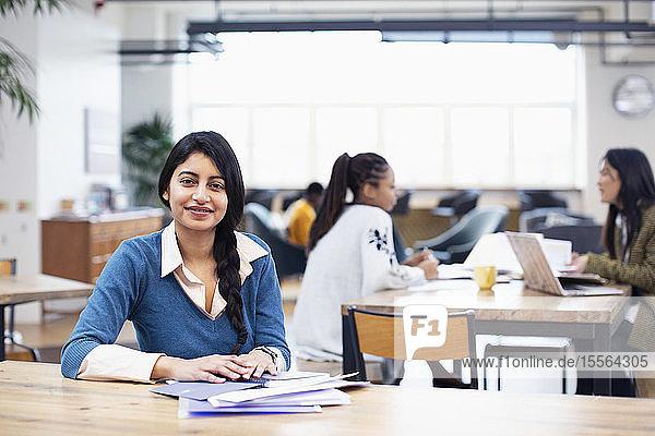 Portrait confident businesswoman working in open plan office