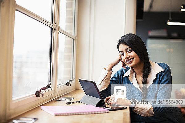 Portrait confident  smiling businesswoman using digital tablet in window