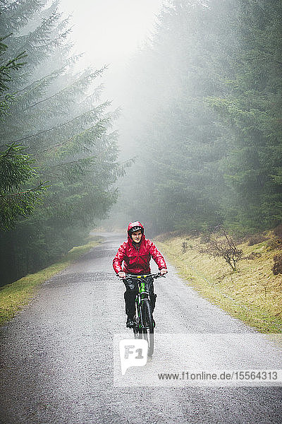 Man mountain biking in rain