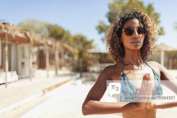 Portrait serene young woman in bikini practicing yoga on sunny patio