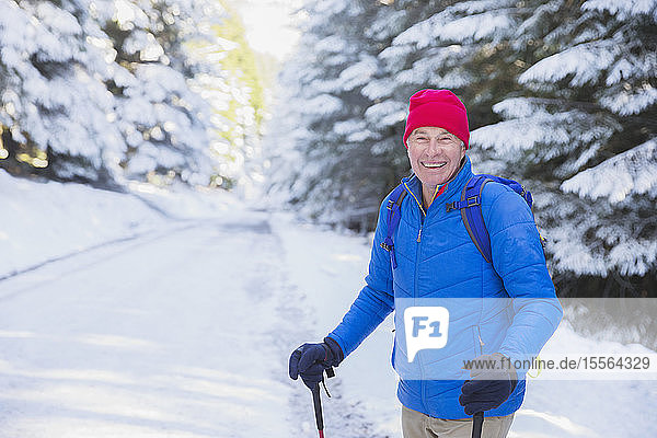 Happy senior man hiking in snow