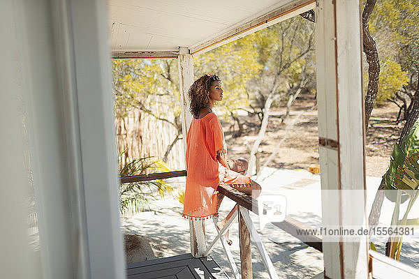 Serene young woman relaxing on beach hut patio