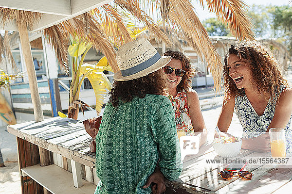 Happy women eating breakfast at sunny beach bar