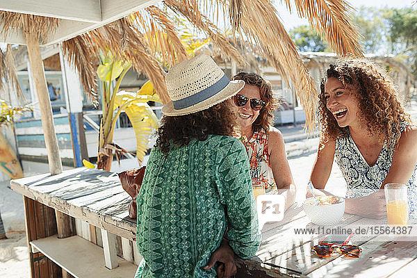 Happy women eating breakfast at sunny beach bar