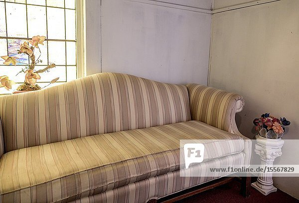 Sofa and artificial flowers in a small room.