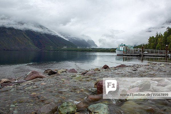 A tourist boat docks along the rocky shoreline at Lake McDonald in Glacier National Park.