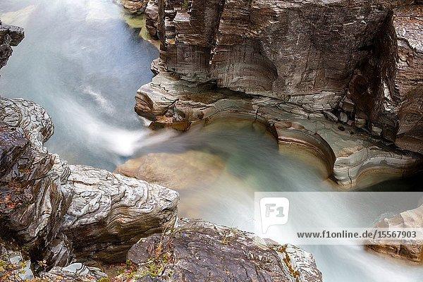 Water surges through a narrow rock canyon in Glacier National Park.