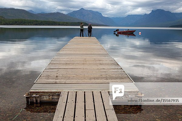 Photographers stand at the end of a long dock at Lake McDonald to capture images of sunset.
